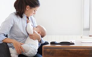 Mom breastfeeding baby while sitting at desk