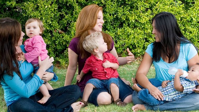 Three moms sitting with their babies in the park