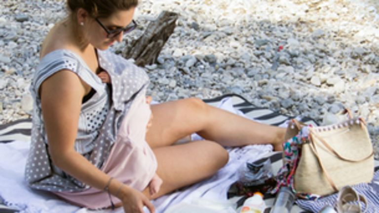 Mom laying on the beach with baby breastfeeding, concealed under a blanket