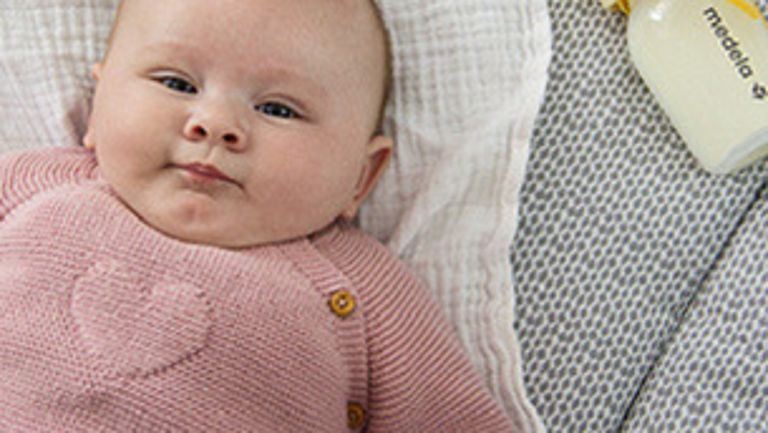 Baby in pink knit sweater laying with a Medela Breast Milk Bottle in the background