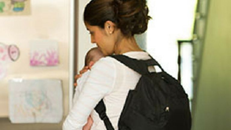 Mom wearing black backpack and holding baby