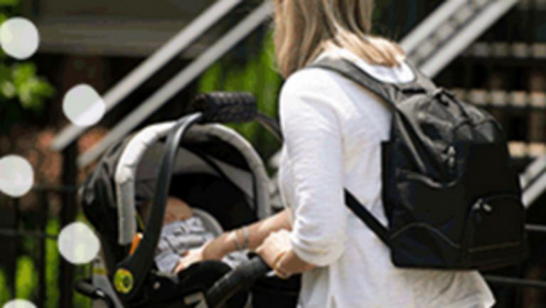 Mom wearing a black backpack pushing baby in stroller