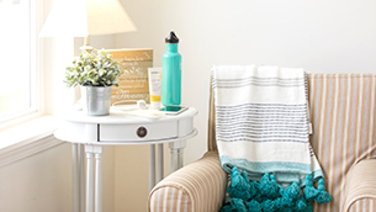 Nursing station with Medela Tender Care Lanolin on side table next to chair