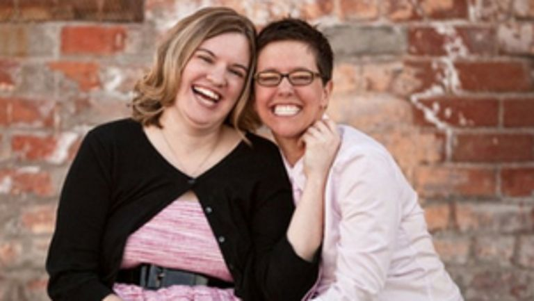 Smiling couple: One woman in pink dress and black cardigan and another woman with glasses and white button-up shirt