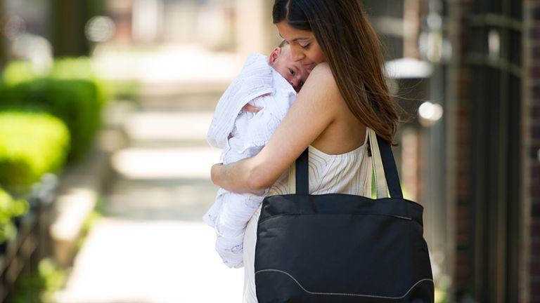 Mom holding baby and carrying Medela portable breast pump bag