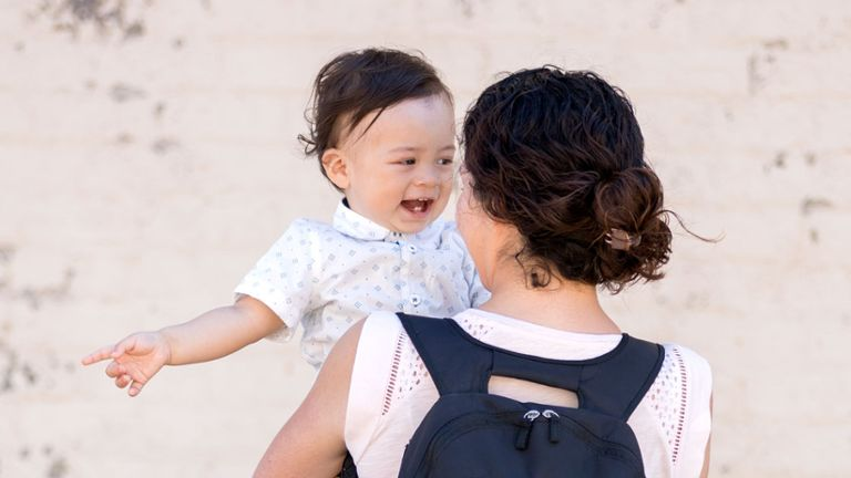 Mom wearing Medela backpack holding smiling child