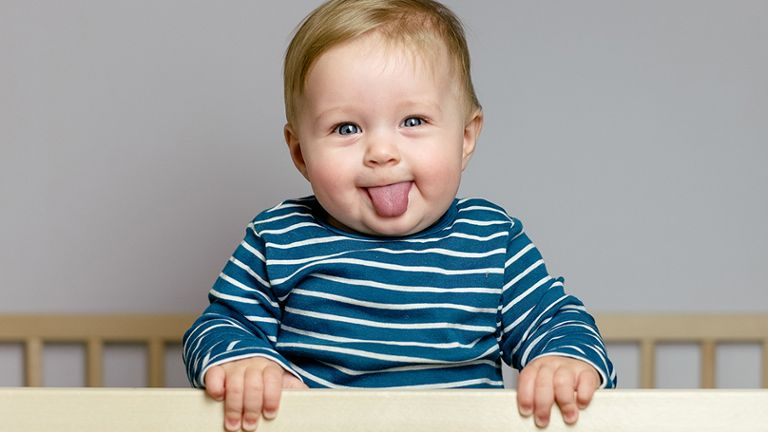 baby standing in crib sticking out tongue and smiling