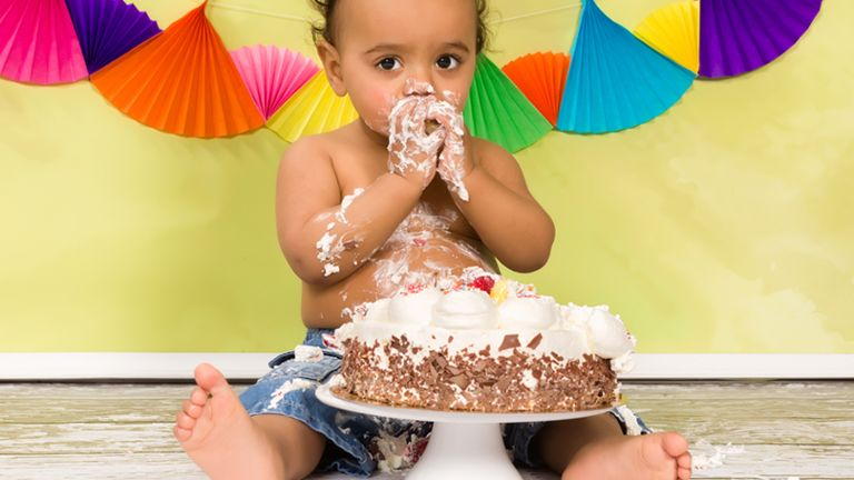 baby with birthday cake and colorful streamers in background