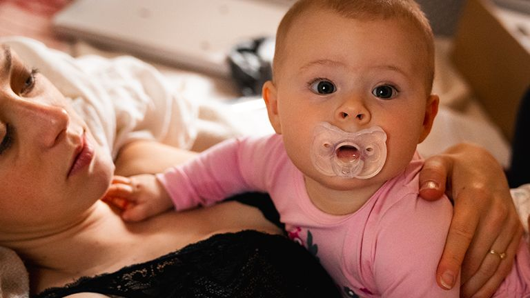 baby with pacifier laying on mom and looking at camera