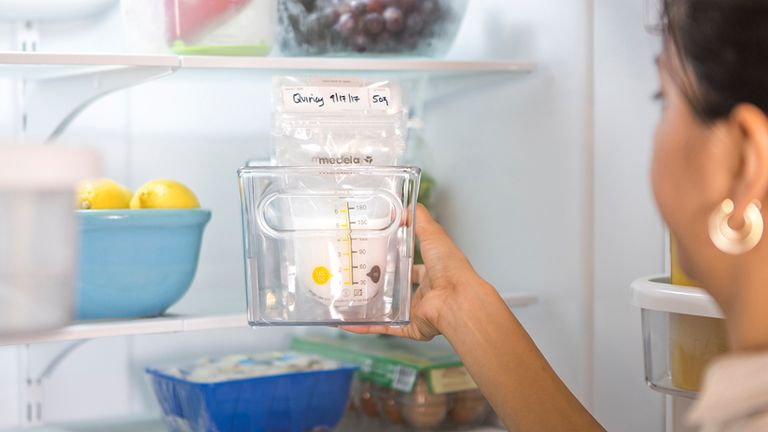 Mom grabbing Medela Breast Milk Storage Bags out of her refrigerator