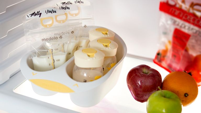 breast milk storage bags and bottles in refrigerator with fruit