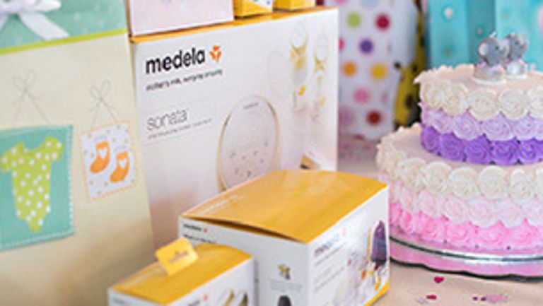 Baby shower Medela gifts next to cake
