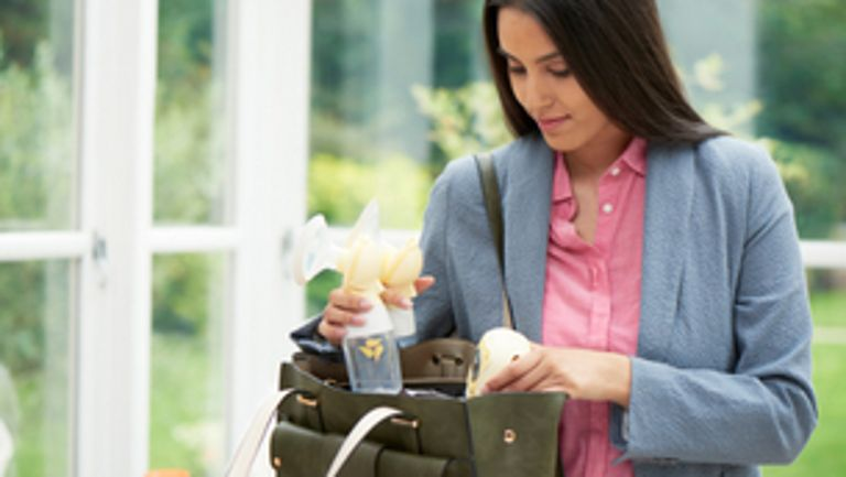 Woman pulling Medela Freestyle Breast Pump out of her purse