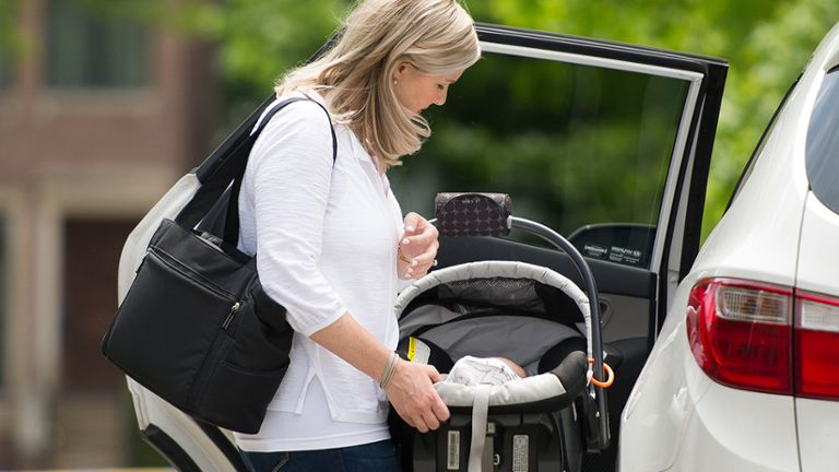 Mom putting baby in car while carrying Medela portable Breast Pump bag