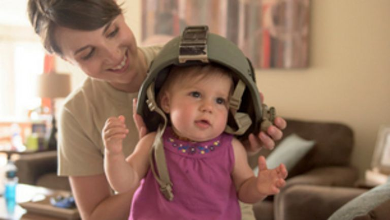 Mom putting an Army helmet on baby's head