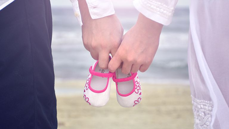Parents holding pink and white baby shoes