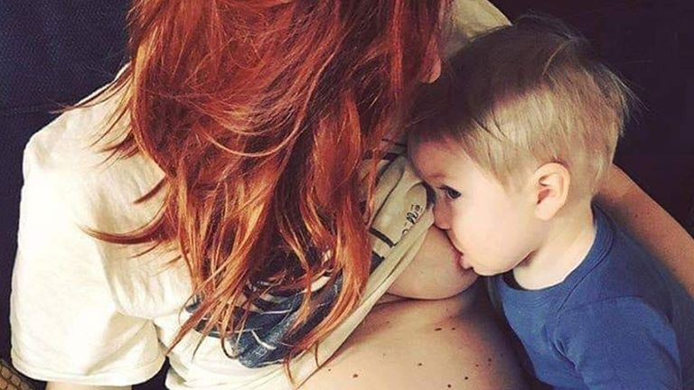 mom with red hair nursing toddler son in blue shirt
