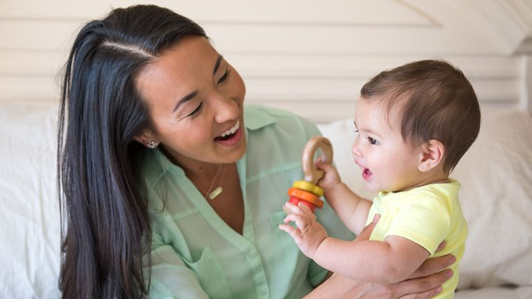 smiling mom and baby with wooden rattle