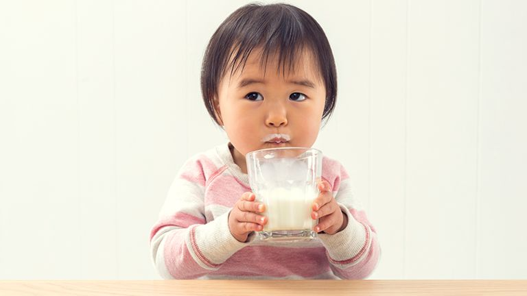 toddler girl drinking milk from glass