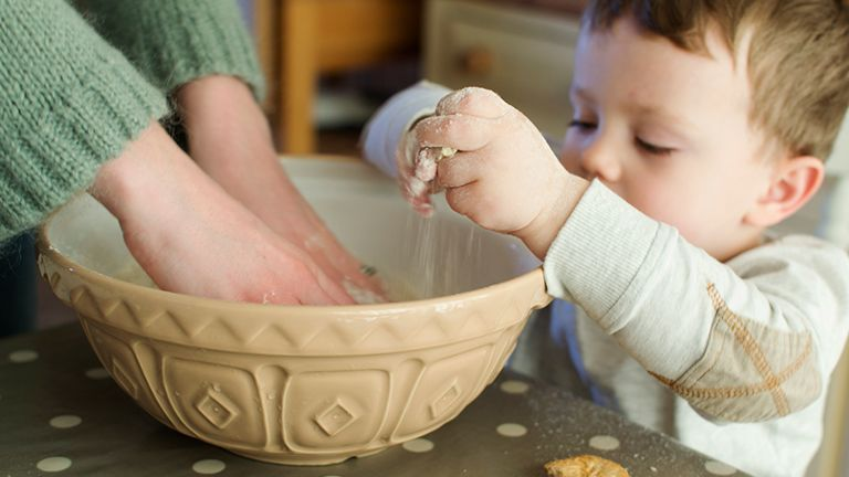 toddler helping bake in tan bowl with flour on hands
