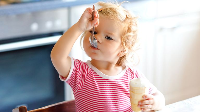 toddler in pink and white striped shirt eating ice cream cone with spoon