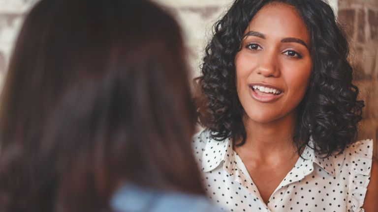 woman smiling in conversation with woman